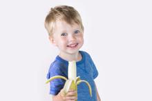 Happy Child Boy Smiling While Eating Banana, Isolated On White Background