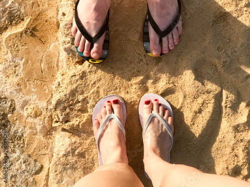 Two pairs of male and female legs with a manicure in slippers, a foot with fingers in flip-flops on a stone sandy floor, earth, beach in a tropical warm hot resort.