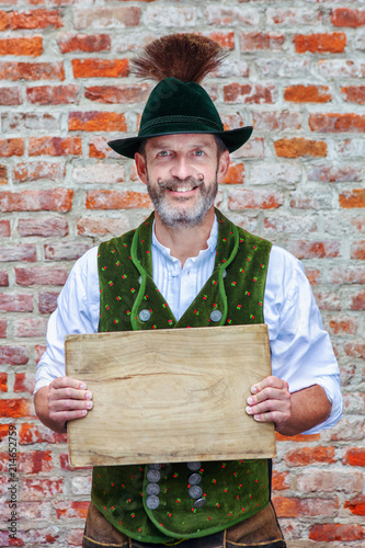 bavarian man holding a wooden plank in his hands Wallpaper Mural
