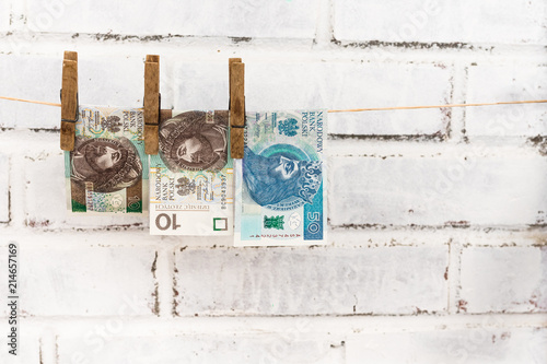 Fotografía  Three Polish zloty bills attached with old wooden washing clips hanging on the s