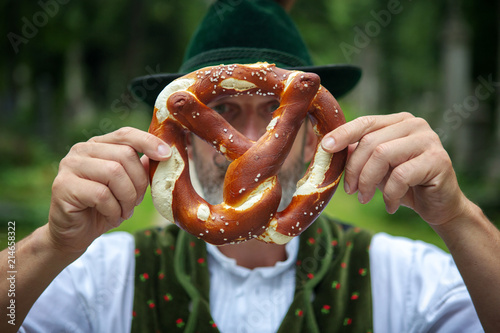 Leinwand Poster bavarian man holding a pretzel in front of his face