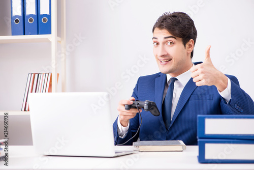 Fotomural Young handsome businessman playing computer games at work office
