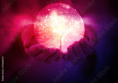 Fotografie, Obraz Magic glowing ball with a flash of light in women's hands on an abstract dark background