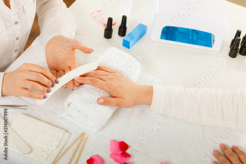 Staande foto Manicure Woman getting manicure done file nails