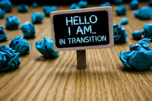 Word Writing Text Hello I Am.. In Transition. Business Concept For Changing Process Progressing Planning New Things Paperclip Hold Black Paperboard With Text Blue Paper Lobs On Wooden Floor.