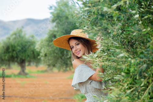 Young redhead girl wearing in dress and hat have a rest in greek olive garden in Heraklion, Crete, Greece