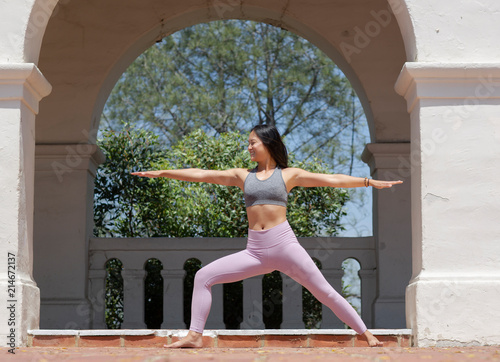 Fotografie, Obraz  Athletic young woman practicing yoga outdoors, doing Warrior two Pose