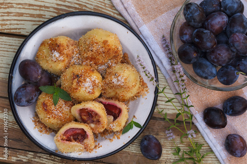 Sweet plum dumplings in metal bowl on wooden table. Homemade dessert with dough and plums.
