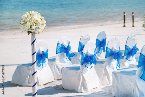 Fotografija  A group of white spandex chairs cover with blue organza sash for beach wedding v