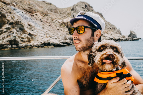 .Young and attractive sailor enjoying a relaxing vacation on his boat wearing his captain cap. Playing with his lovely brown spanish water dog on the yatch Sunny summer day. Lifestyle