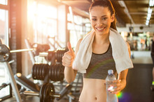 Beautiful Smiling Young Fit Woman With Towel And Water Bottle Showing Thumb Up In Gym