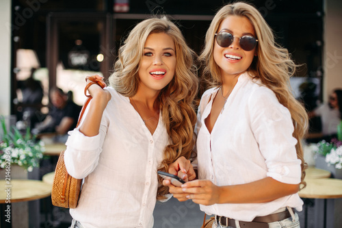 Photo  Fashionable and beautiful female twins using smartphone posing near stylish restaurant outdoors