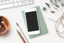 Bright Feminine Smartphone Mockup With Mint Notebook, Eucalyptus Twigs, Accessories And A Wooden Bowl On A White Boho Styled Desk. Flat Lay.