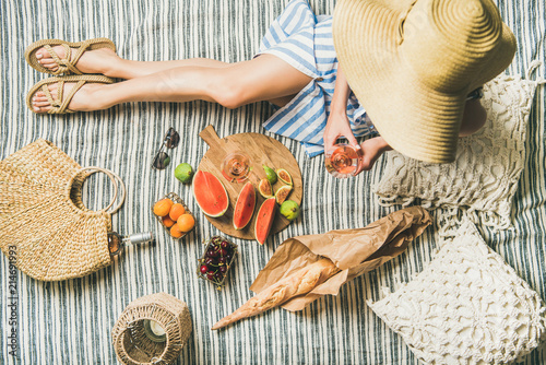 Summer picnic setting. Woman in linen striped dress and straw sunhat sitting with glass of rose wine in hand, fresh fruit and baguette on blanket, top view. Outdoor gathering or lunch concept