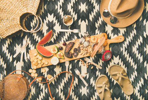 Summer picnic setting. Flat-lay of fresh fruit, smoked sausage, nuts, cheese, pate, cracker on board and woman straw accessories over linen blanket background, top view. Outdoor gathering or lunch