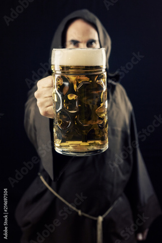 Photo A bearded friar (Franciscan religious man) offering a giant mug of beer to the viewer, made even bigger by the perspective