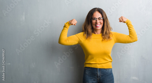 Fotografie, Obraz  Middle age hispanic woman over grey wall wearing glasses showing arms muscles smiling proud