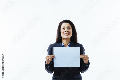 Fotografía Portrait of a woman with big smile and grey jacket holding blank sign, isolated