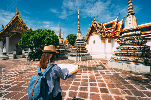 Fotomural Young woman traveler with backpack and hat looking the Map in Wat Pho at Bangkok Thailand