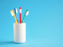 Four Colored Toothbrushes In A Glass On A Light Blue Background