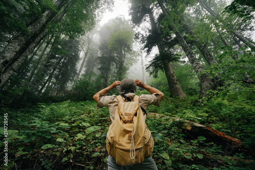 фотография  the male tourist in shorts is standing with his back, hat and with a beige backpack in the fog of the forest hand in hand, a gesture of admiration