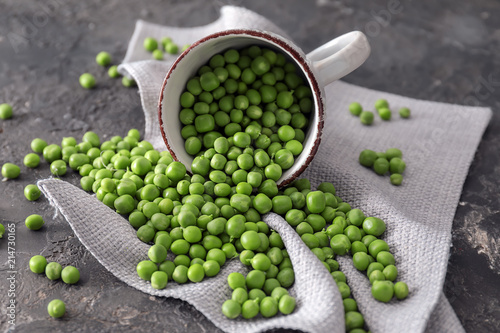 Carta da parati Cup with delicious fresh green peas on grey textured background