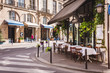 canvas print picture - Cozy street with tables of cafe  in Paris, France