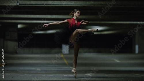 Fototapeta Portrait of ballet dancer on pointe in an underground car park