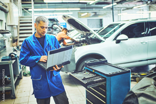 fototapeta na lodówkę mechanic man with automotive diagnostic scanner and clipboard checking car system at workshop