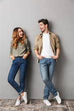 Full Length Portrait Of A Smiling Young Couple Standing