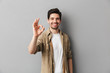 Portrait of a happy young casual man showing ok gesture