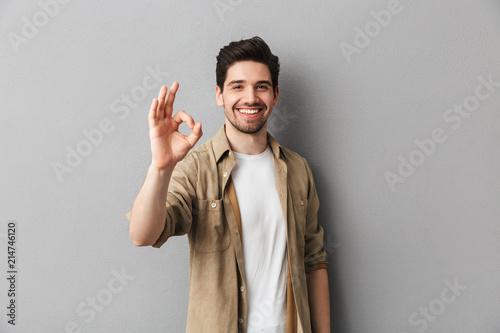 Fototapeta Portrait of a happy young casual man showing ok gesture obraz