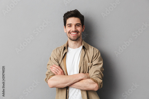 Obraz Portrait of a happy young casual man standing - fototapety do salonu