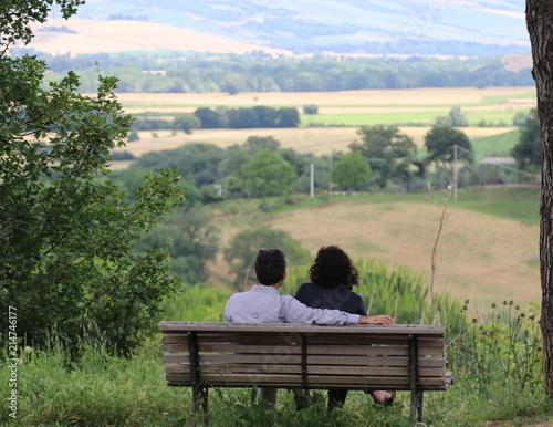 Fotografie, Obraz  Coppia di giovani seduti su una panchina a guardare il panorama