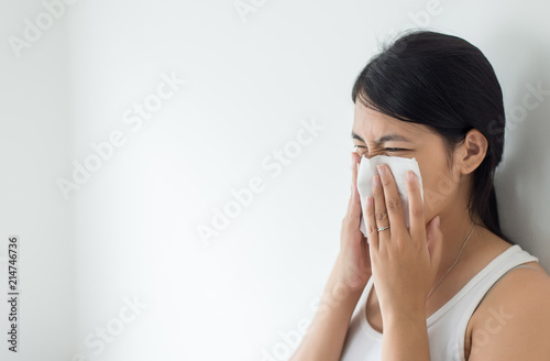 Valokuva  Young asian woman with cold blowing and runny nose in home,sick woman sneezing,C