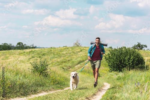 traveler running with dog on path on summer meadow Fototapeta