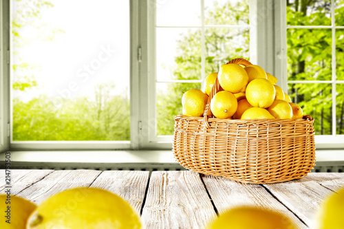 Fresh yellow lemon on white wooden table and free space for your bottle or glass. Window background of summer time.