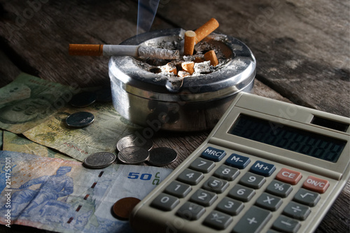 Cigarette And Calculator With Money In Concept How Many Cost You Pay To Year Month Day