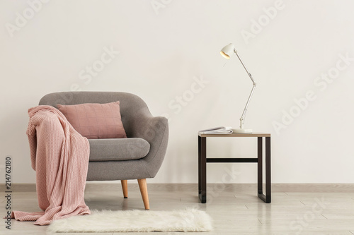 Valokuva  Comfortable armchair with table and lamp near light wall
