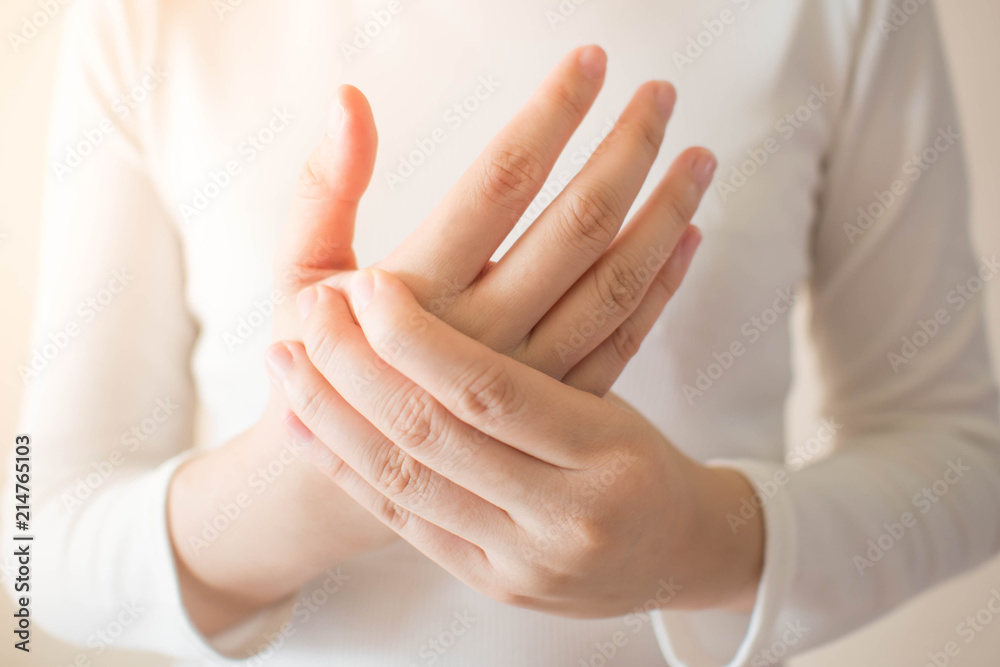 Fototapeta Young female in white t-shirt suffering from pain in hands and massaging her painful hands. Causes of hurt include carpal tunnel syndrome, fractures, arthritis or trigger finger. Health care concept.