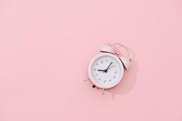 Light pink vintage alarm clock on pink color background