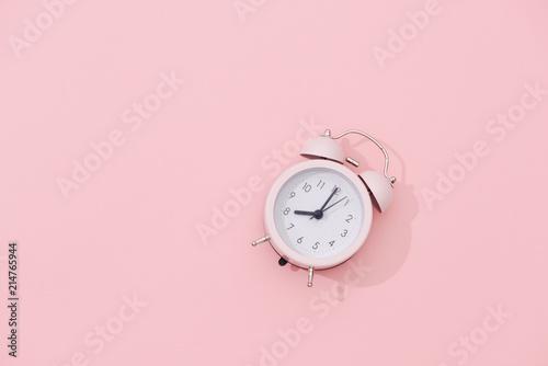 Fototapeta Light pink vintage alarm clock on pink color background obraz