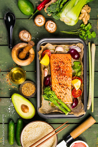 Photo  Baking dish with fresh raw salmon steak, vegetables  and seasoni