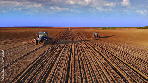 Fototapeta Farmers in tractors seeding, sowing agricultural crops in field at sunset obraz