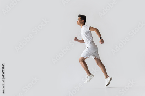 Fotografie, Tablou  side view of young asian male athlete running on grey background
