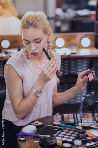 Professional makeup artist with bright makeup fixing her cheekbones putting makeup on