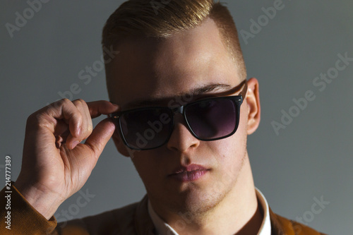 Poster  Handsome man in leather jacket touches his sunglasses in grey studio, close up