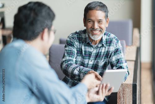 Happy old short beard asian man sitting, smiling and listen to partner that showing presentation on smart digital tablet Wallpaper Mural