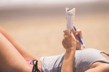 Lay Down Young Beautiful Woman Close Up On Body Relaxed And Hae Nice Time Doing A Words Play On Paper. Beach Vacation Leisure Activity Under The Sunlight. Skin Tanner Concept In Holiday