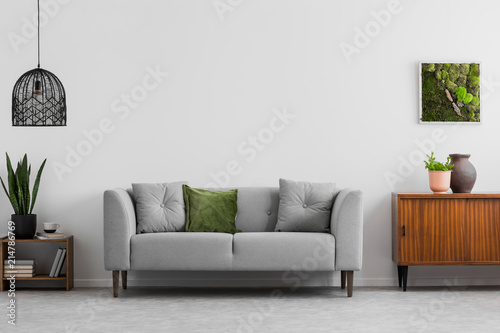 Fototapeta Grey sofa with pillows next to wooden cupboard in living room interior with lamp and poster. Real photo obraz na płótnie